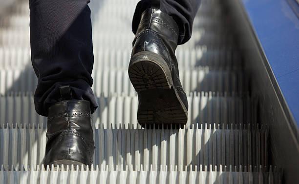 male feet walking in boots up escalator - alt kısım stok fotoğraflar ve resimler