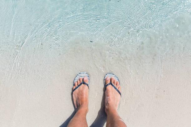 männliche füße tragen weibliche flip-flops am strand - salzwasser sandalen stock-fotos und bilder