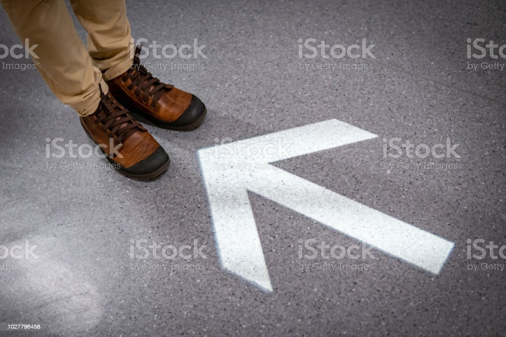 Male feet with casual shoes standing at the end of light arrowhead sign on the floor. Keep moving forward concept. Urban lifestyle fashion. stock photo