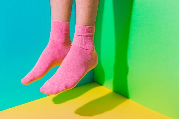 Männliche Füße mit haariger Haut in Socken, die in der Luft über fetten Hintergrund in der Ecke mit starken Schatten fliegen. – Foto