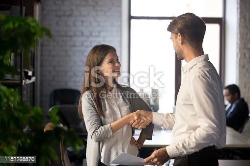 843963182 istock photo Male female colleagues greeting each other with handshake 1152268870