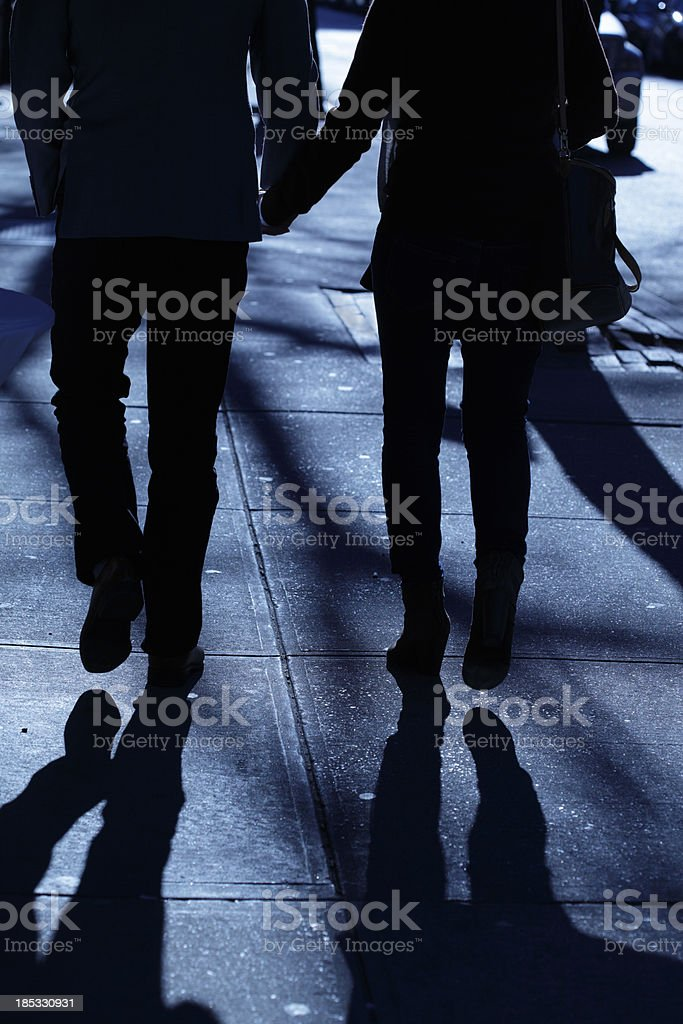 Male female holding hands walking in blue night shadows royalty-free stock photo