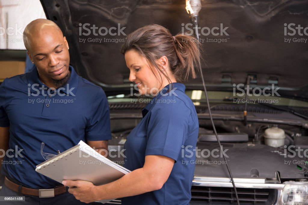 Male, female mechanics working together in auto repair shop. stock photo