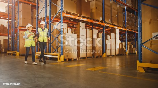istock Male, Female Supervisors Holding Digital Tablet Talk about Product Delivery in Retail Warehouse full of Shelves with Goods in Cardboard Boxes. Workers in Distribution Logistics Center. Low Angle Shot 1284193448