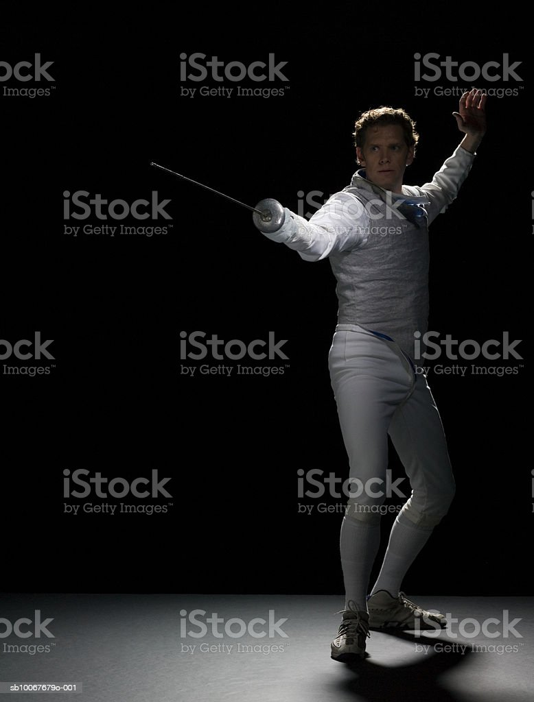 Male fencer practicing, studio shot royalty-free stock photo
