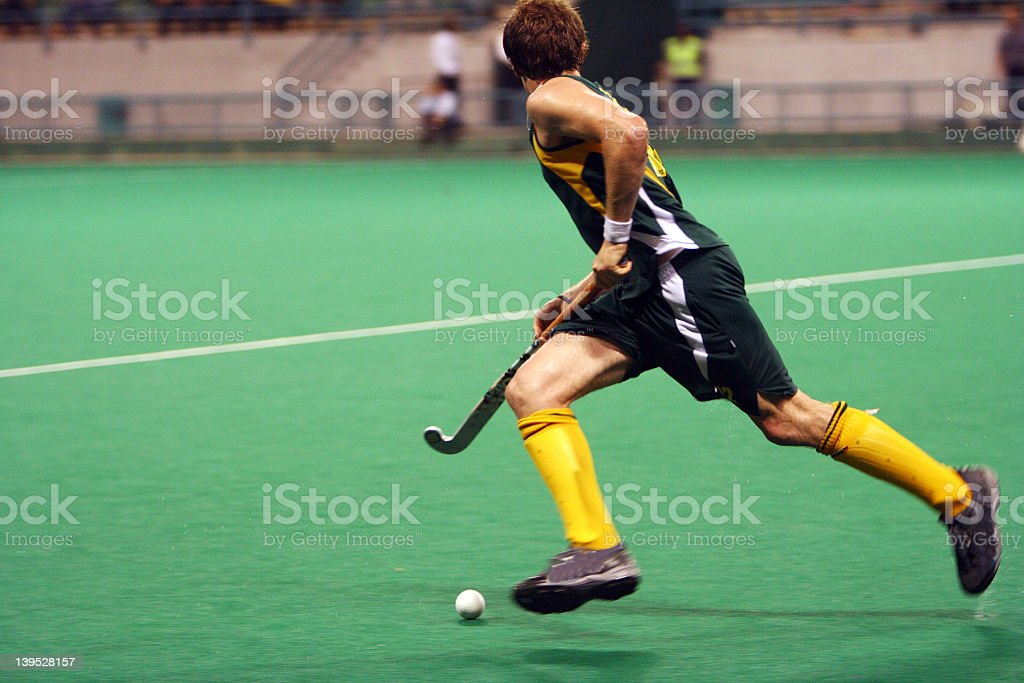 Male field hockey player running with ball stock photo