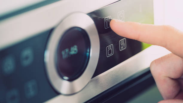 Male finger is touching the button of modern panel of electric oven. stock photo
