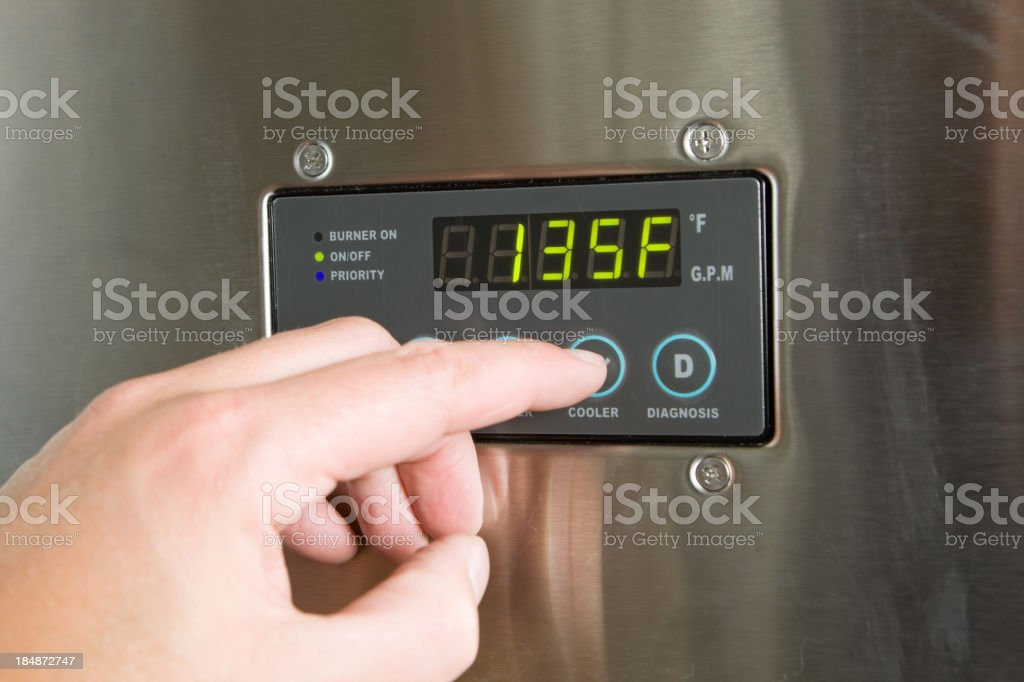Male Finger Turning Down Tankless Water Heater Temperature stock photo