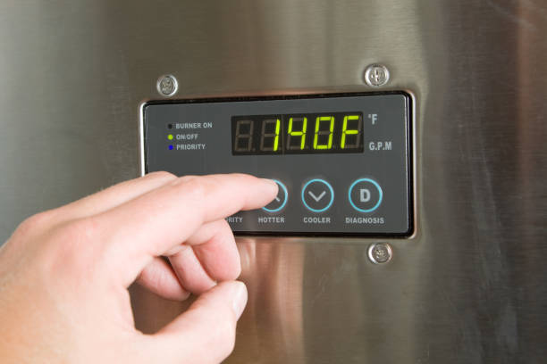 Male Finger Turning Up Tankless Water Heater Temperature stock photo