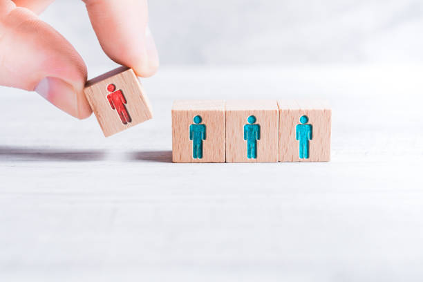 Male Fingers Adding A Block With A Different Colored Man Icon To 3 Blocks With Equal Colored Man Icons On A Table - Leadership Concept Arranged By Male Fingers On A White Table prettige verrassingen stock pictures, royalty-free photos & images