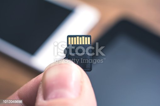 Two Male Fingers Holding A Micro SD Card With Tablet And Smartphone In Background, Extent Disk Space Concept