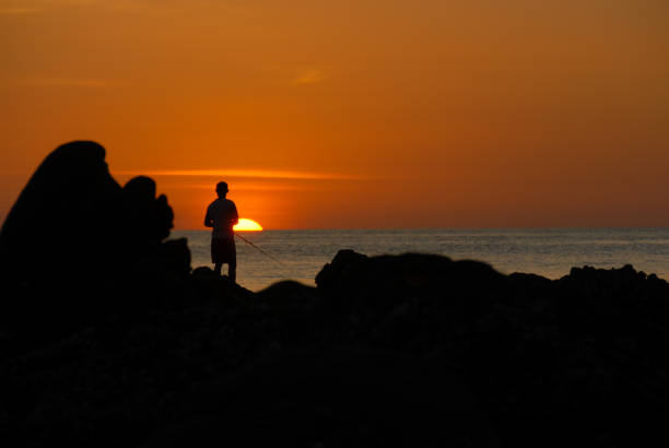 Male fisherman standing on the rocks during sunset stock photo
