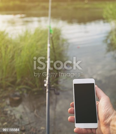992209122istockphoto Male fisherman uses the phone on fishing sitting on the shores of lake 991155584