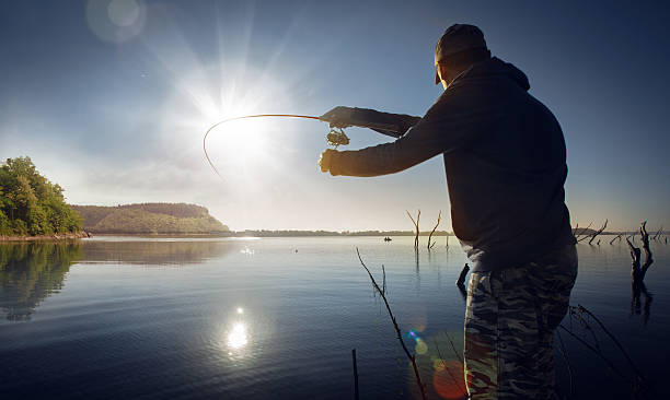 Male fishing at sunset on lake Man fishing on sunset freshwater fishing stock pictures, royalty-free photos & images