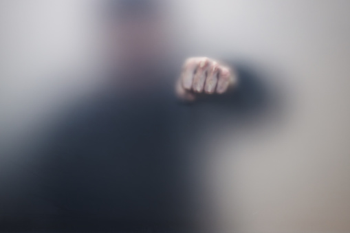 istock Male fist behind matte glass, abstract photo 1210608780