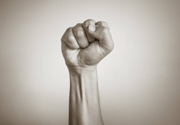 male fist in the air isolated on white background. - forza foto e immagini stock