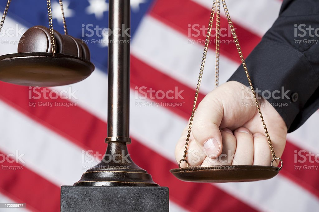 Male fist pressing scale of justice royalty-free stock photo