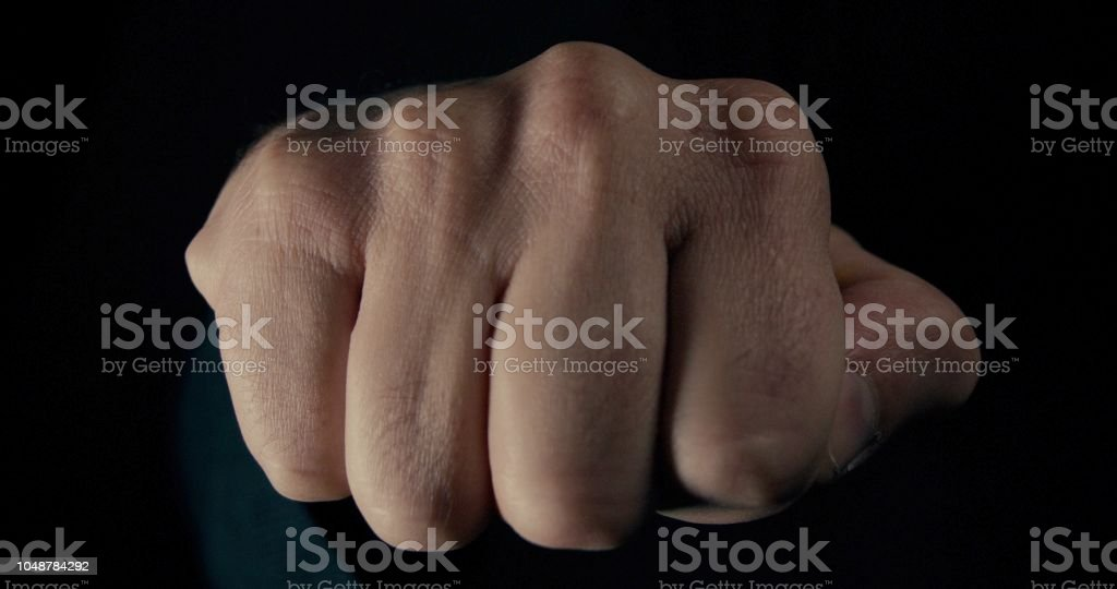 Male fist punching in a powerful aggressive manor stock photo