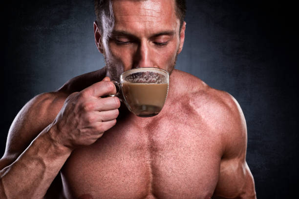 Male fitness athlete Studio shot of male fitness athlete while drinking coffee. caffeine stock pictures, royalty-free photos & images