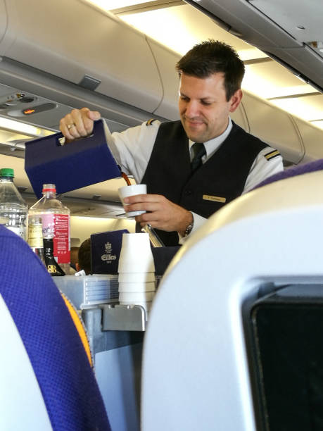 A male flight attendant serving in the economy class. stock photo