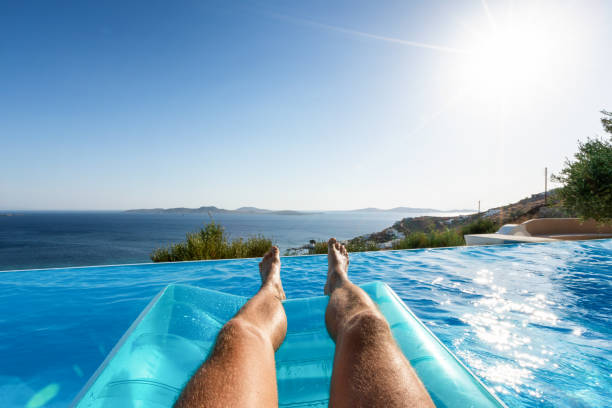 Male floating over blue pool water with view to the sea stock photo