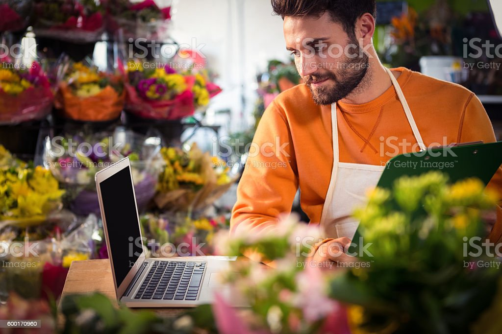 Male florist checking order in laptop stock photo