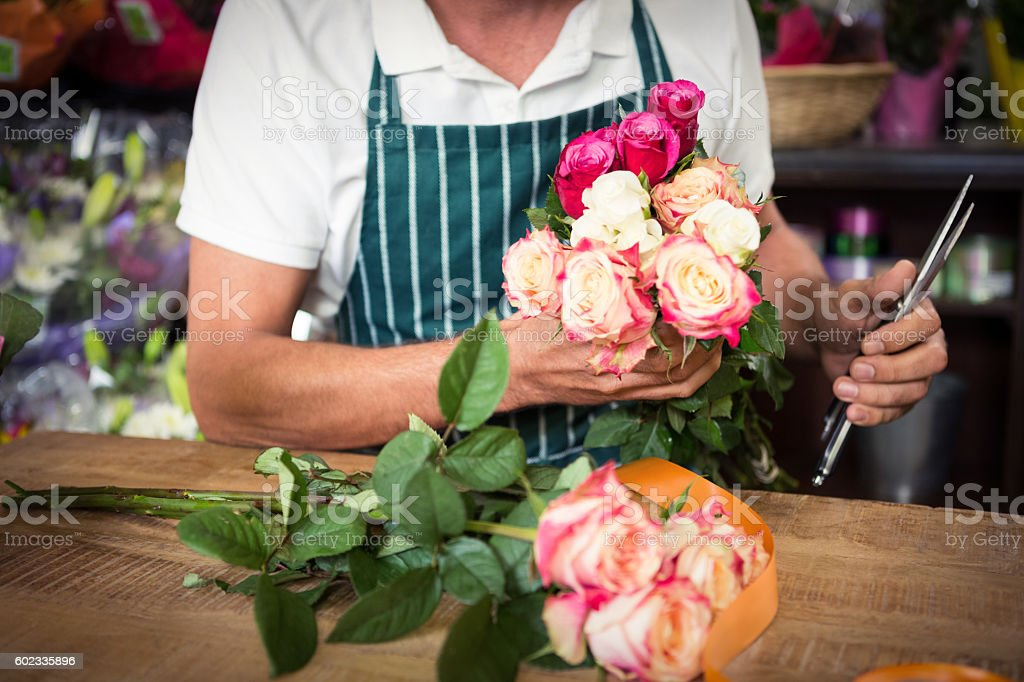 Male florist holding bunch of roses and shears – Foto