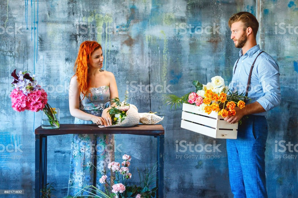 Male positive smiling florist man holding wooden box with flower...
