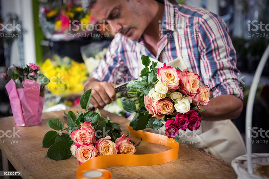 Male florist preparing bouquet of flower stock photo