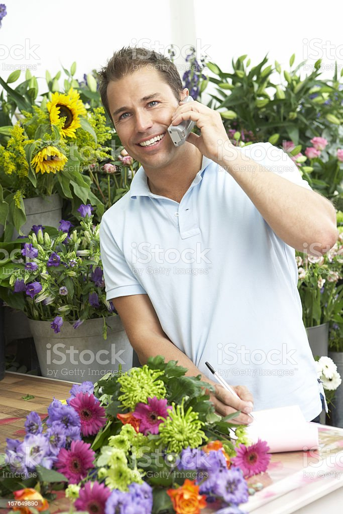 Male Florist Taking Telephone Order In Shop royalty-free stock photo