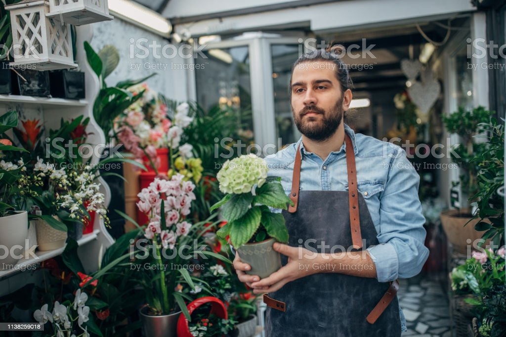 One young male florist working at the flower shop, wearing uniform.