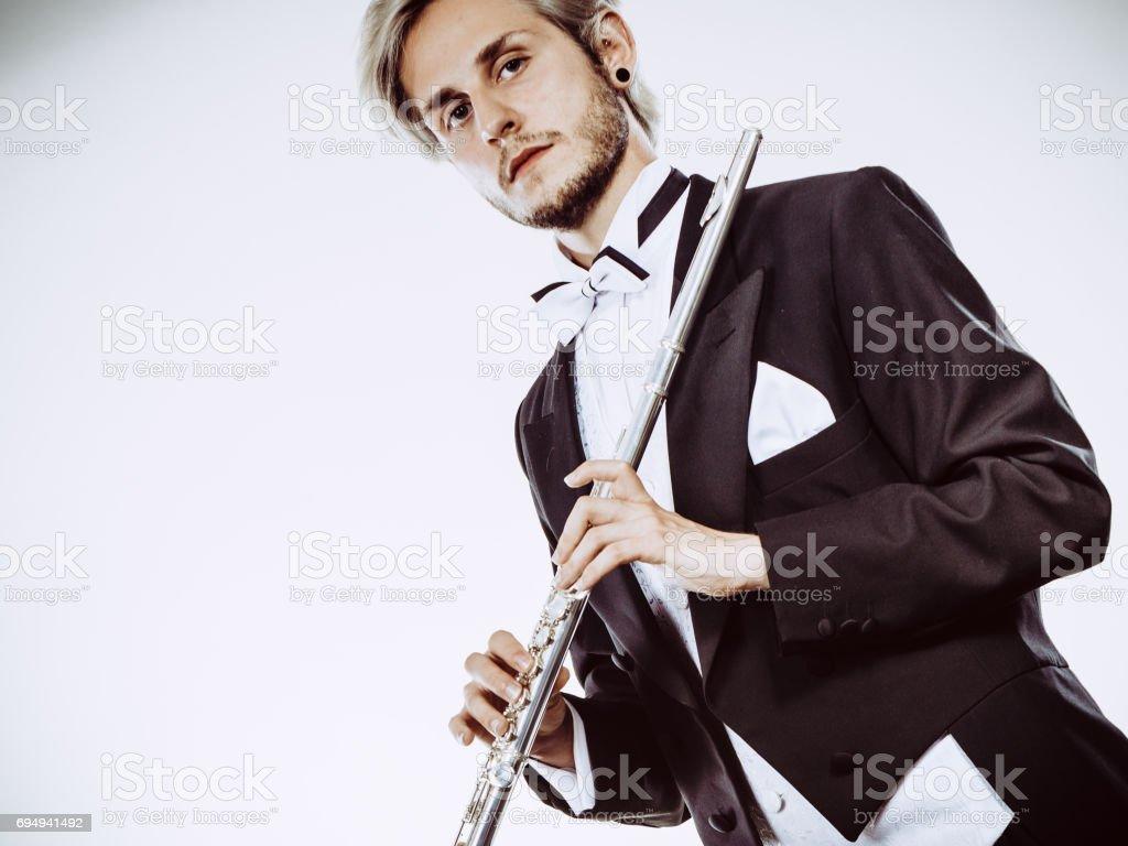 Male flutist wearing tailcoat holds flute stock photo