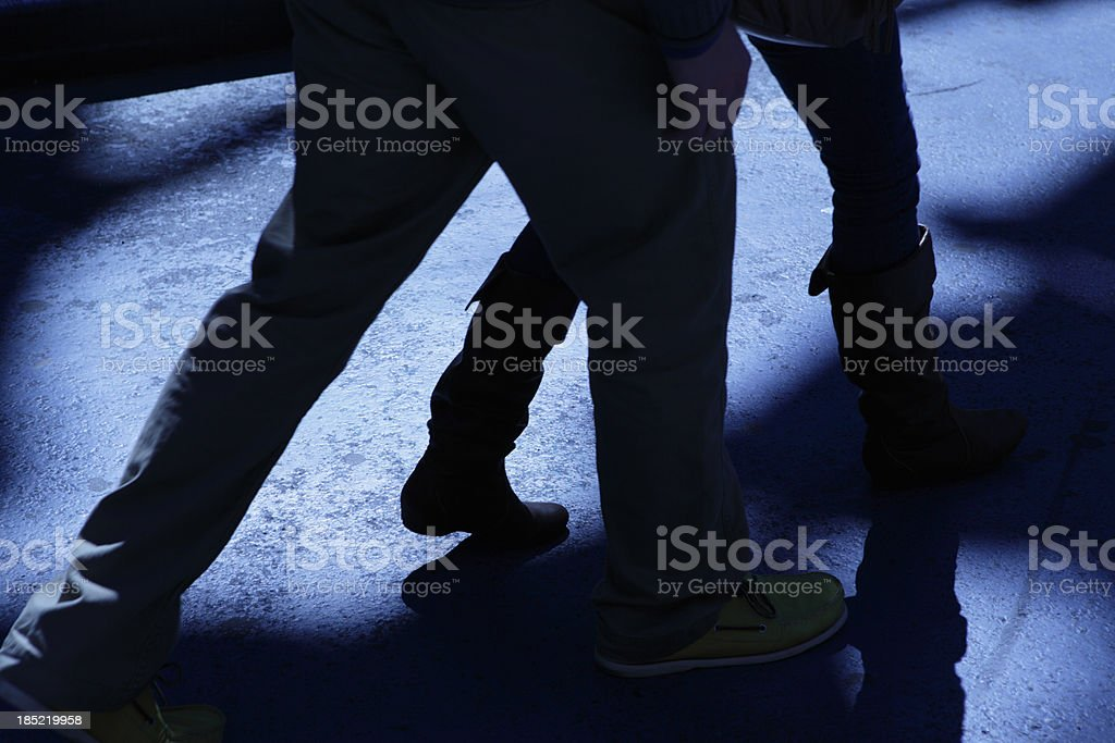 Male following attacking female in blue night shadows stock photo