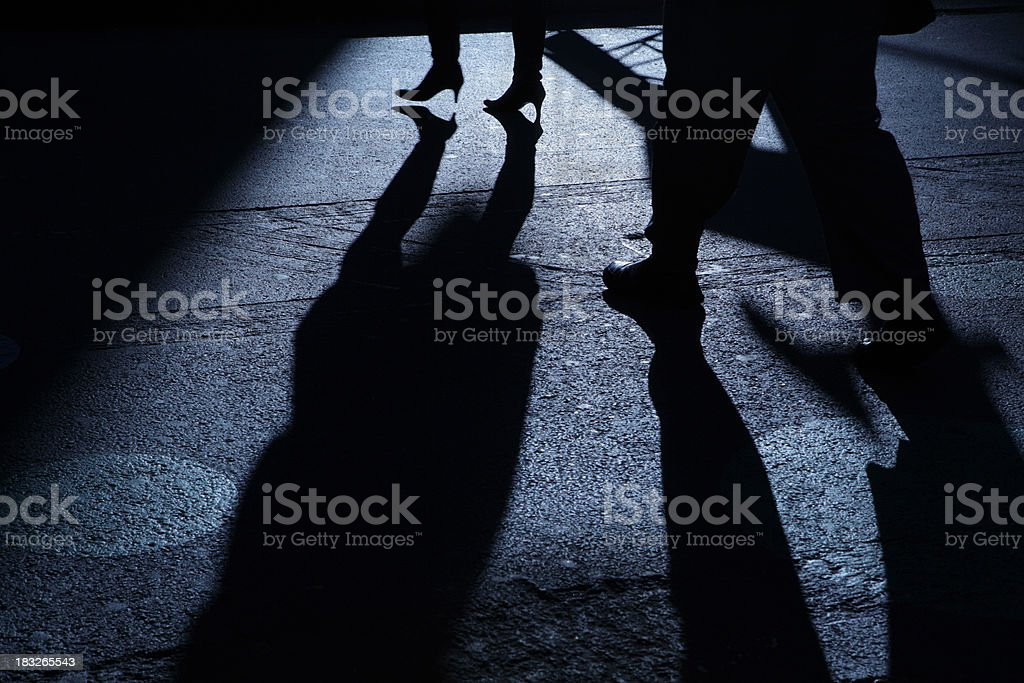 Male following female into blue night shadows stock photo