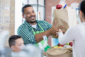 Confident male food bank volunteer together with his son give out healthy food to people in need.