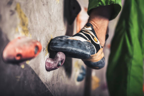 male foot on climbing wall - clambering stock photos and pictures