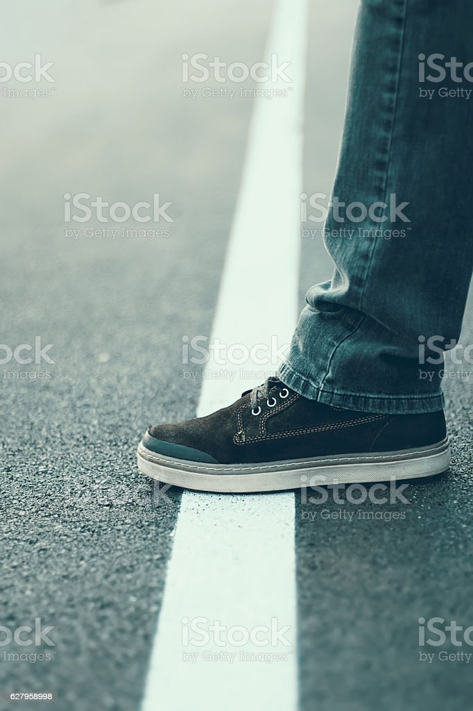 Male foot standing on the white line. Crossing line concept. stock photo