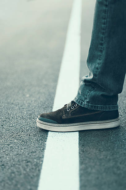male foot standing on the white line. crossing line concept. - 地理的境界 ストックフォトと画像