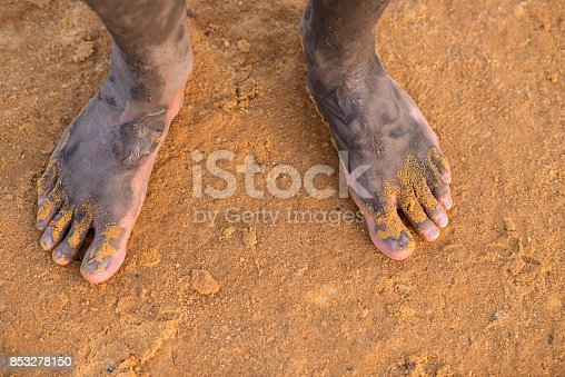 Man's foot with mineral mud of Dead Sea on salty beach sand.
