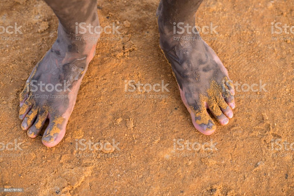 Male foot with mineral mud of Dead Sea on salty beach sand. stock photo