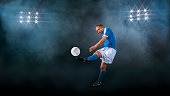 Male footballer kicking ball
