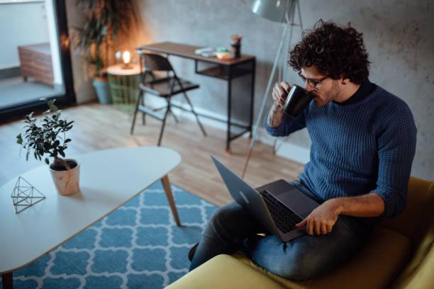 Männlicher Freiberufler, der am Laptop arbeitet und Kaffee trinkt – Foto
