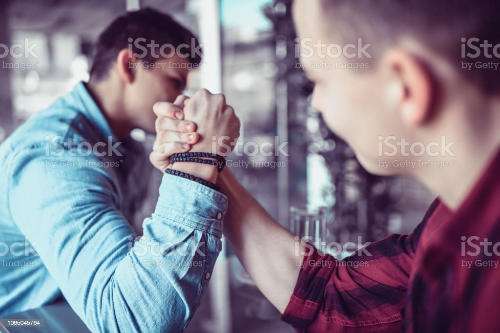 Male Friends Arm Wrestling On A Bar Table stock photo