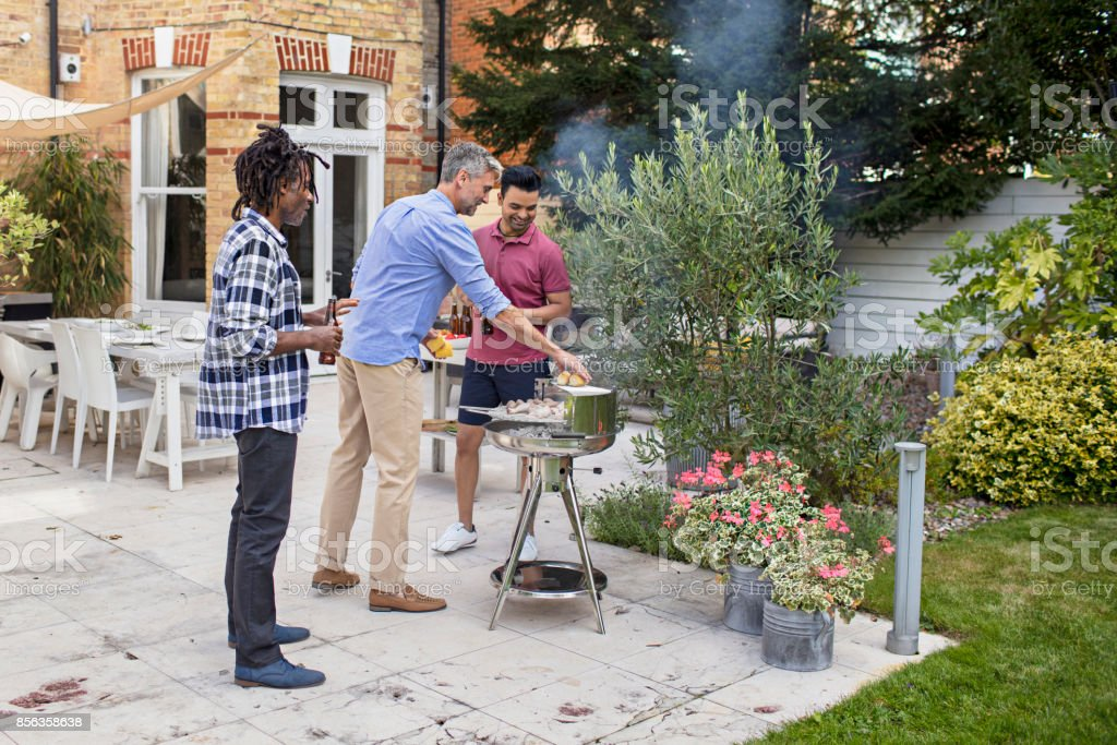 Male friends barbecuing in back yard stock photo
