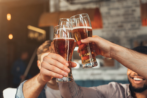 Male friends clinking beer glasses in bar, closeup