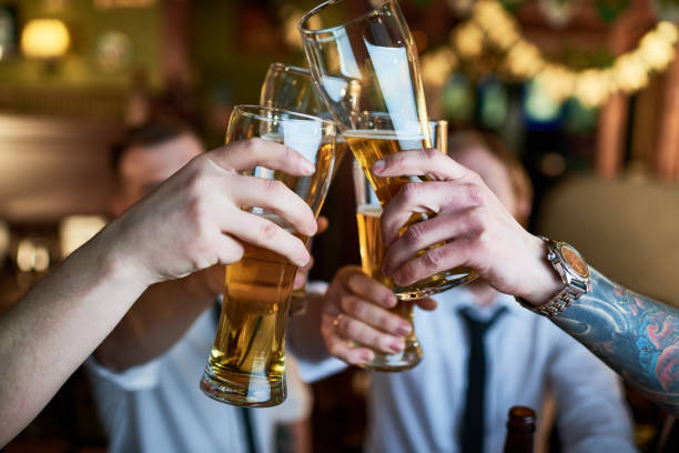 male friends clinking glasses of craft beer - stag night stock pictures, royalty-free photos & images