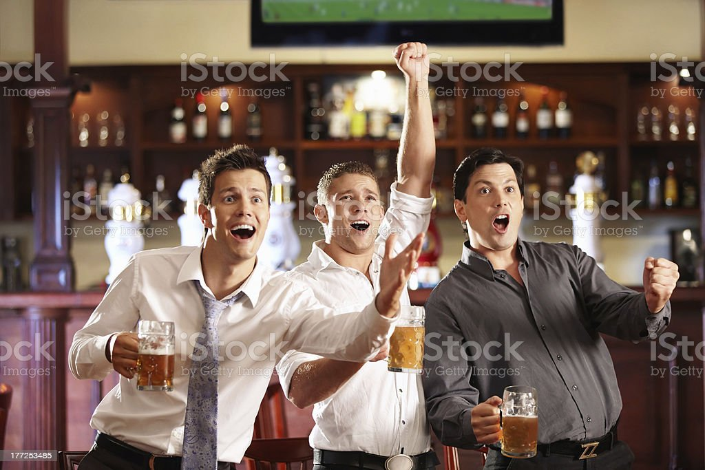 Male friends drinking beer and celebrating royalty-free stock photo
