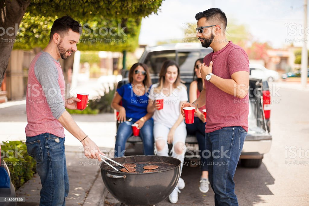 Male friends grilling hamburgers outdoors stock photo