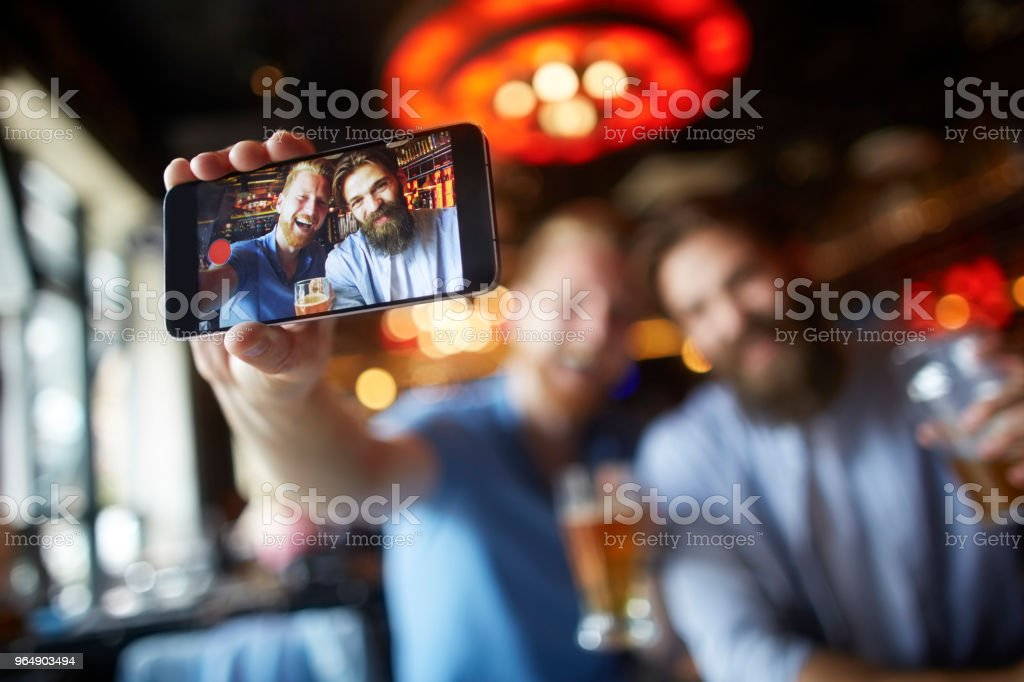 Male friends in the bar posing for a selfie royalty-free stock photo