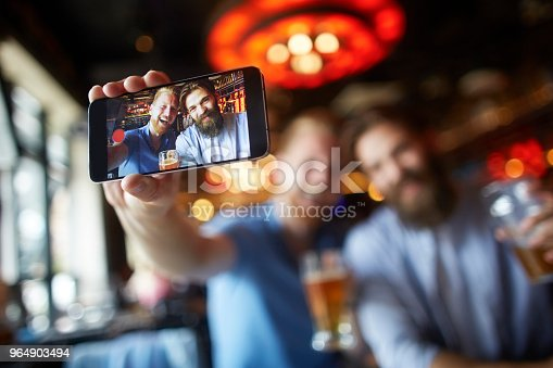 istock Male friends in the bar posing for a selfie 964903494